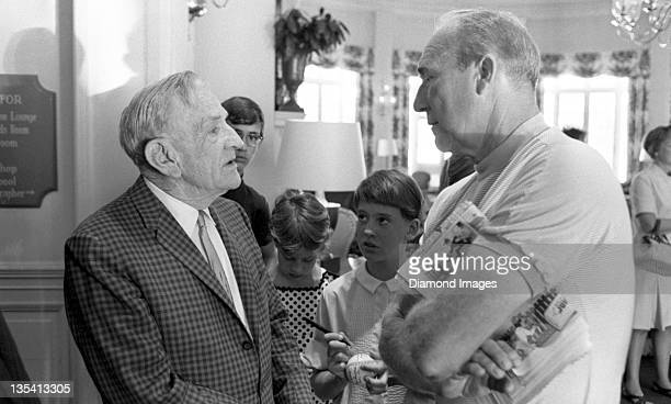 Baseball Hall of Famer Casey Stengel talks with fellow Hall of Famer Charles Red Ruffing while a young girl awaits an opportunity to request their...