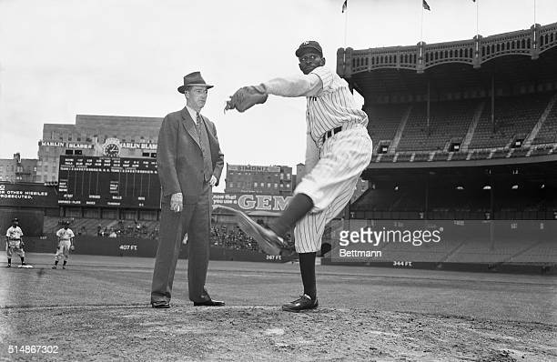 Baseball Hall of Famer Grover Cleveland Alexander stands on the pitcher's mound at Yankee Stadium and watches pitcher Satchel Paige at work. Paige is...