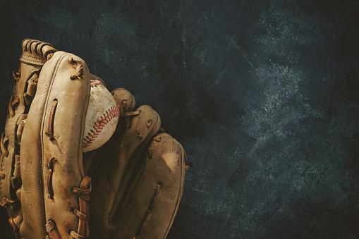 Baseball in glove with copy space on dark grunge background. 1128976026