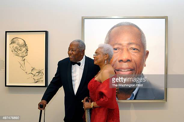 Baseball legend Hank Aaron with his wife Billye Aaron pause for a photograph in front of his portrait hanging at the National Portrait Gallery...
