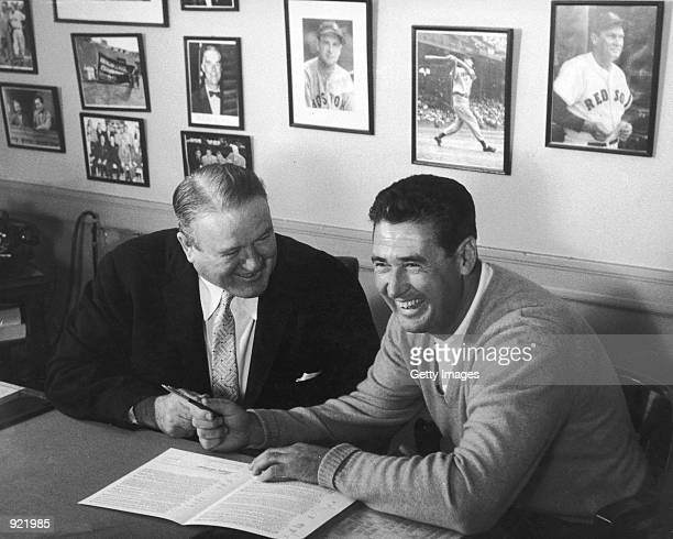 Baseball legend Ted Williams of the Boston Red Sox signs a baseball contract as Boston Manager Joe Cronin looks on in 1958. The 83-year-old Williams,...