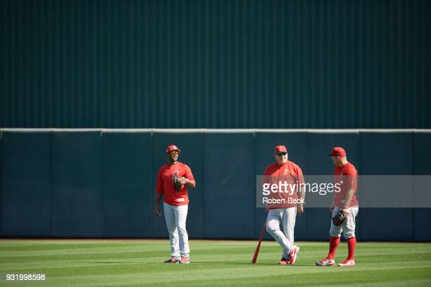 Los Angeles Angels of Anaheim manager Mike Scioscia in outfield holding fungo bat with Justin Upton and Mike Trout before spring training B game at...