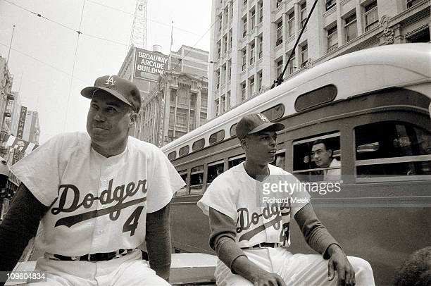 Los Angeles Dodgers Duke Snider and teammate Charlie Neal riding bus during welcoming parade on South Broadway before opening day vs San Francisco...