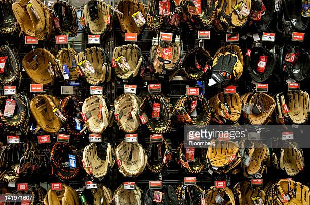 Baseball mitts are displayed for sale at a Modell's retail location in Times Square in New York US on Tuesday March 27 2012 Manufacturers in the US...