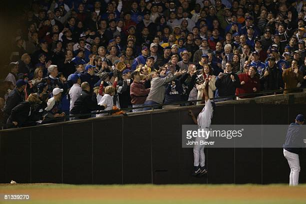 Baseball NLCS Playoffs Chicago Cubs Moises Alou in action attempting foul ball catch foul vs Florida Marlins Cubs fan Steve Bartman reaching and...