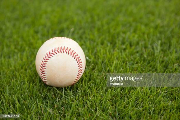 Baseball on grass at baseball field at baseball game