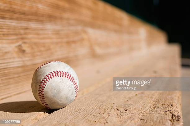 A baseball on the dugout bench