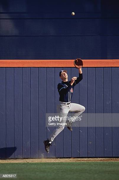 Baseball outfielder leaping to catch ball