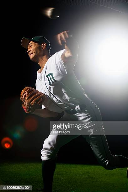 Baseball pitcher releasing ball, grimacing, (lens flare, blurred motion)