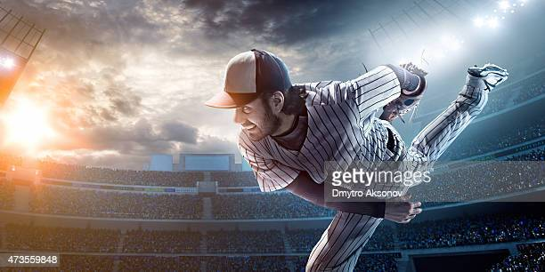 A baseball player after he has just thrown a ball