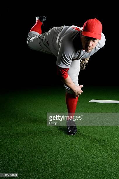A baseball player after making a pitch