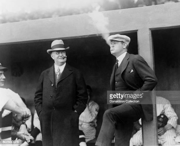 Baseball player Babe Ruth in the Washington dugout smoking a cigar in the Washington Dugout as President Ban Johnson looks on on April 12 1922
