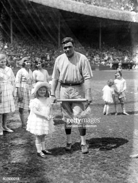 Baseball player Babe Ruth on the field in Yankees uniform with a little girl in 1921 in New York New York