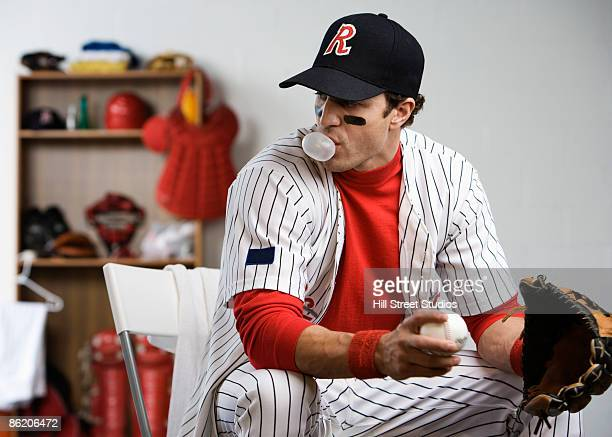 Baseball player blowing bubble with gum in locker room