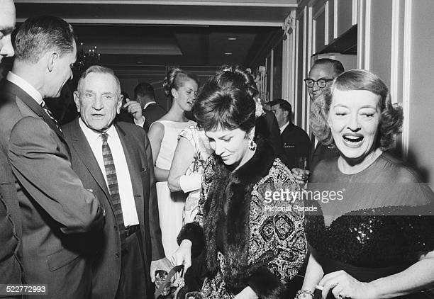 Baseball player Casey Stengel and actresses Gina Lollobrigida and Bette Davis attending an anniversary party circa 1960