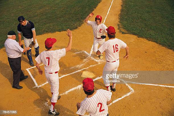 baseball player crossing home plate greeted by teammates - home run stock pictures, royalty-free photos & images