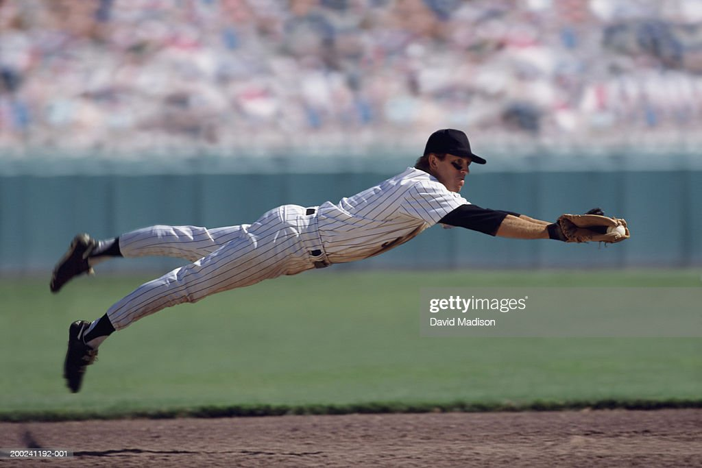 Baseball player diving to catch ball (Digital Composite) : Stock Photo