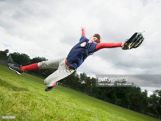 Baseball player diving to catch ball