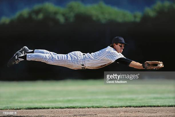 baseball player diving to catch ball, side view - diving to the ground stock pictures, royalty-free photos & images