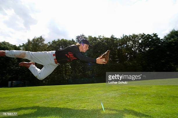 A baseball player diving to catch the ball