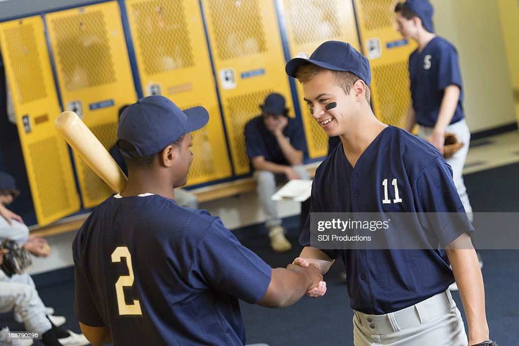 Baseball Player Greeting New Teammate In Locker Room Stock Photo