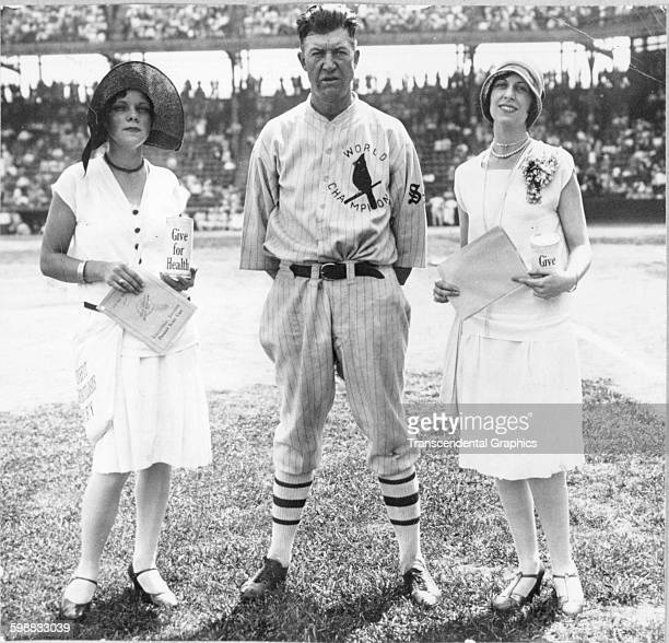 Baseball player Grover Cleveland Alexander poses with two women both of whom hold charity jars before a game at Sportsmans Park St Louis Missouri 1927