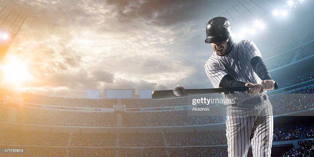 Baseball player hitting a ball in stadium : Stock Photo