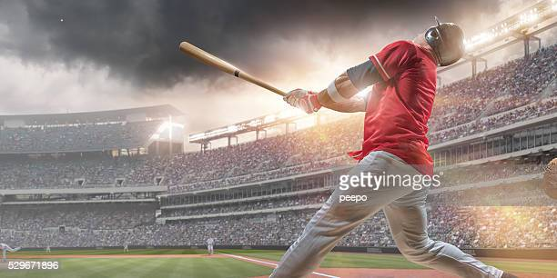 baseball player hitting ball during baseball game in outdoor stadium - batting stock pictures, royalty-free photos & images