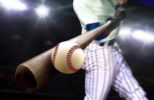 Baseball player hitting ball with bat in close up under stadium spotlights 1176475684