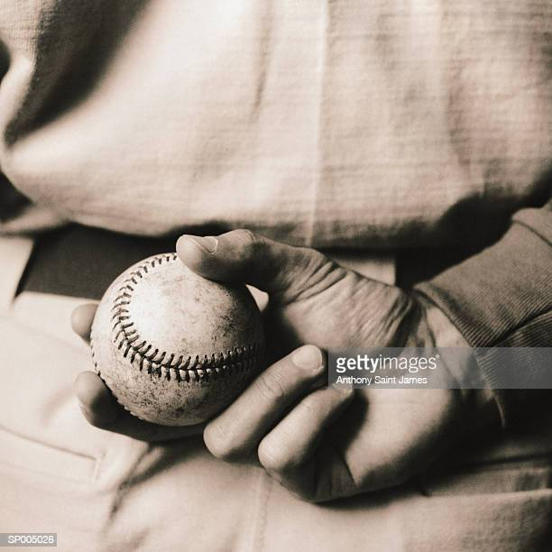 Baseball player holding ball, rear view, close-up (toned B&W)