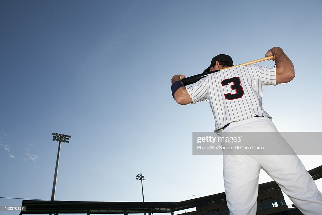 Baseball player holding bat, rear view : Stock Photo