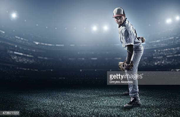 A baseball player in a stadium about to make a pitch