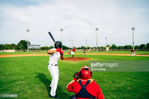 baseball player in batter's box watching thrown pitch - baseball catcher stock pictures, royalty-free photos & images