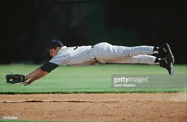 baseball player in mid-air catching ball. california, usa. - diving to the ground stock pictures, royalty-free photos & images