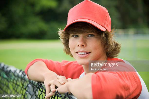 Baseball player (13-15) leaning against chainlink fence, portrait