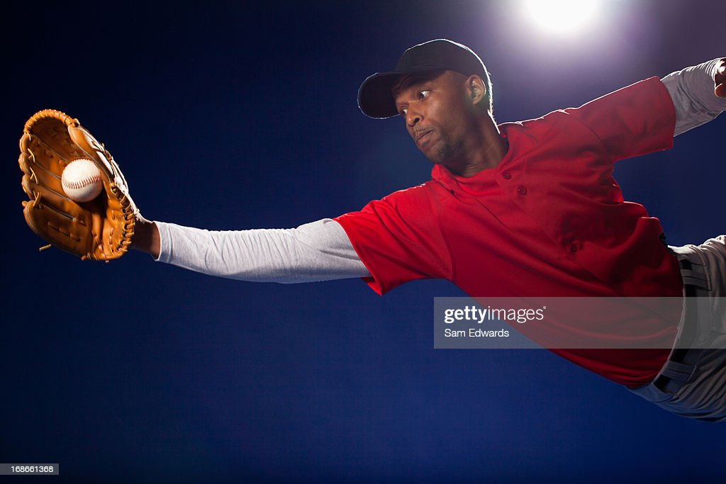 Baseball player lunging for ball : Stock Photo