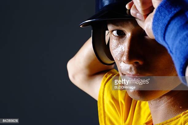 Baseball player putting cap on, studio shot