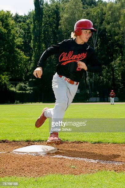 A baseball player running over a base