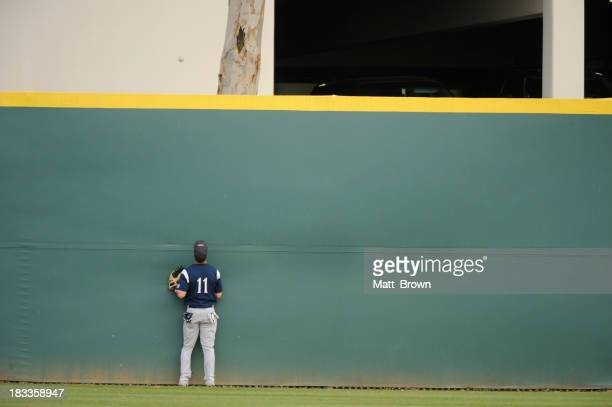 A baseball player searching desperately for his ball