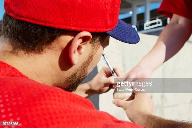 Baseball player signing baseball