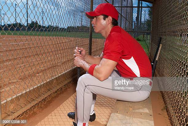 baseball player sitting by wire mesh fence, side view - banquillo deportivo fotografías e imágenes de stock