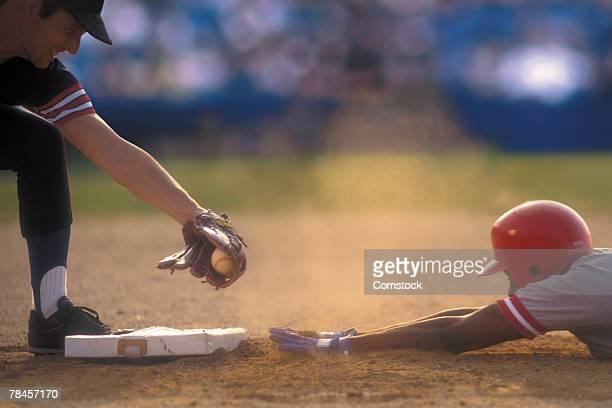 Baseball player sliding into base as baseman tags him