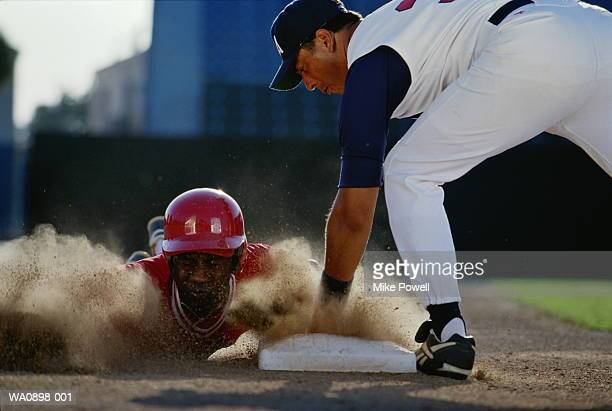 baseball, player sliding into base watched by opponent - só adultos imagens e fotografias de stock