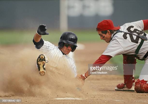 baseball player sliding into home plate, being tagged by catcher - baseball player stock pictures, royalty-free photos & images