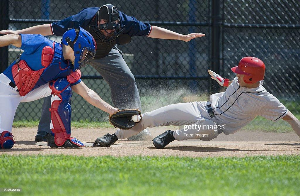 Baseball player sliding into home plate : Stock Photo