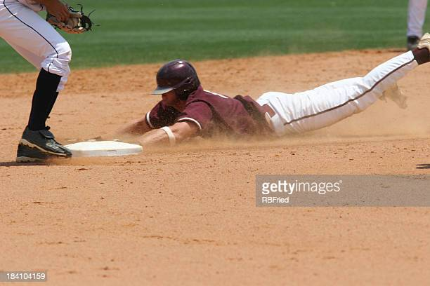 A baseball player sliding to the plate