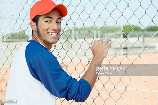 baseball player standing behind fence - sideburn stock pictures, royalty-free photos & images