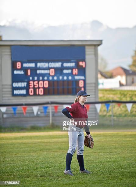 Baseball player Standing in Left Field with Scoreboard behind