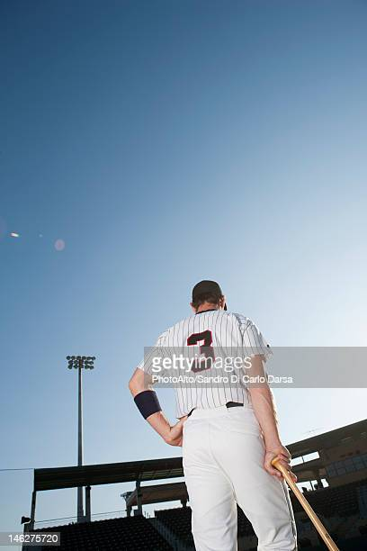 baseball player standing with hand on hip, rear view - baseball uniform stock pictures, royalty-free photos & images