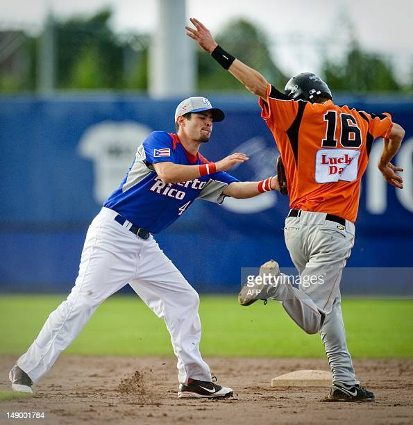 Baseball player Stijn van der Meer of The Netherlands is touched out by Juan Diaz between first and second base of Puerto Rico in the semi finals...